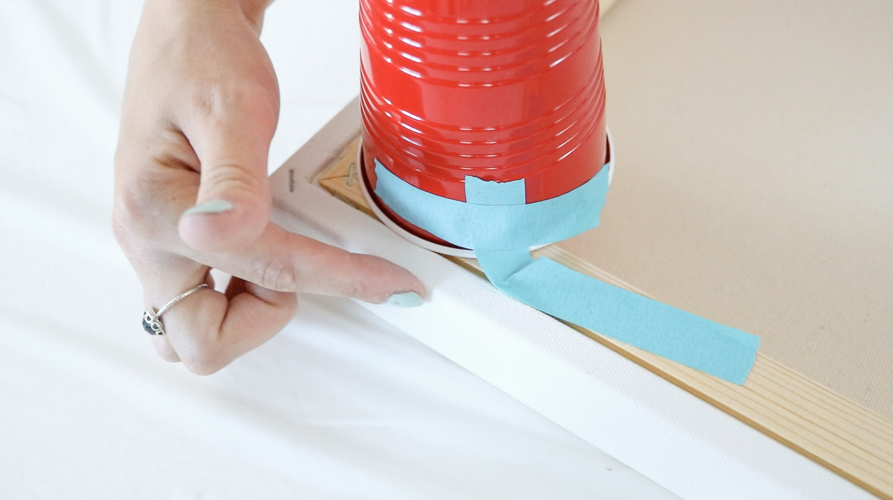 taping cups to the bottom of a canvas