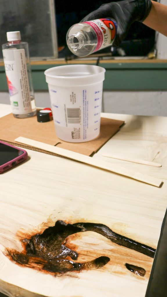 fills holes with resin for our DIY coffee table