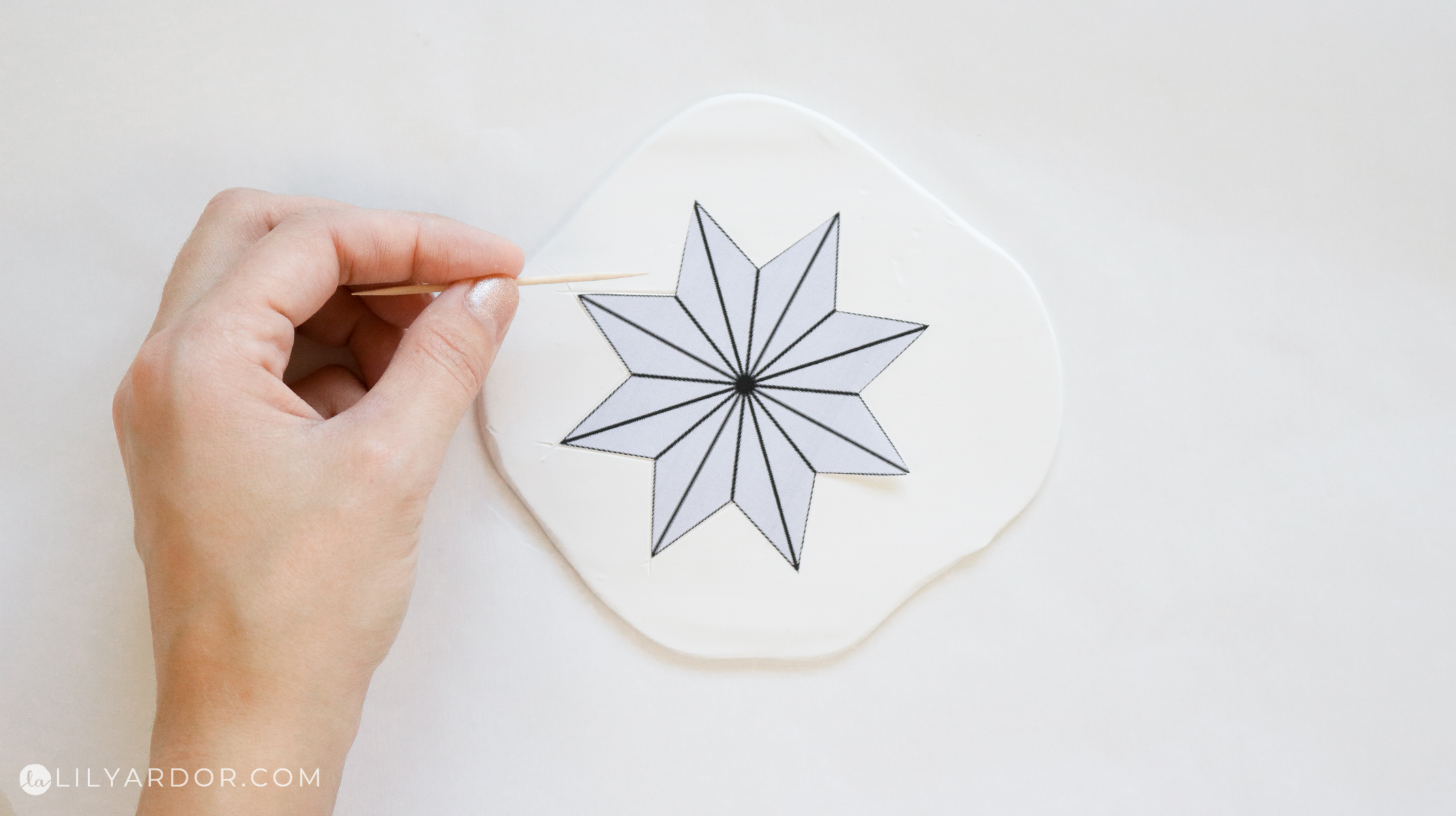 tracing the star on pylomer clay with a toothpick