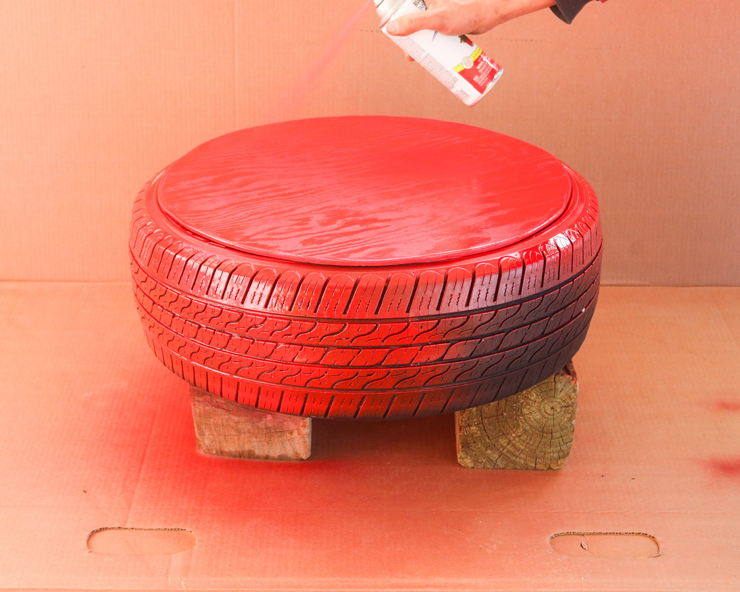 spray painting the tire red for a christmas ornament