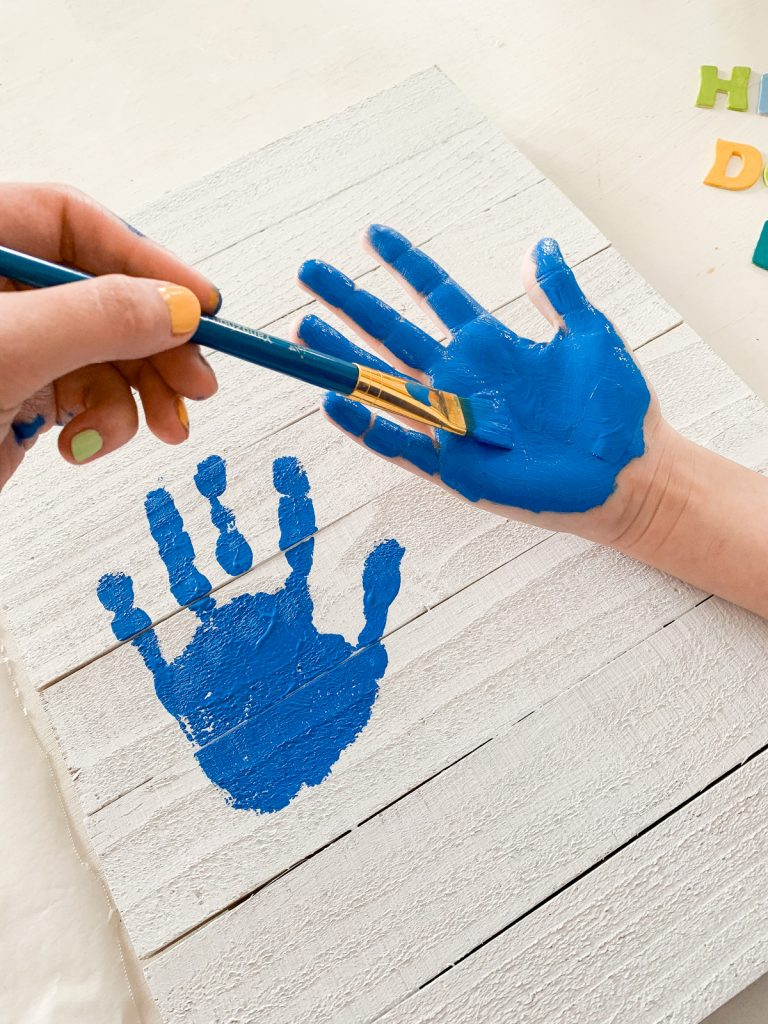 painting hand for stamping handprint father's day gift